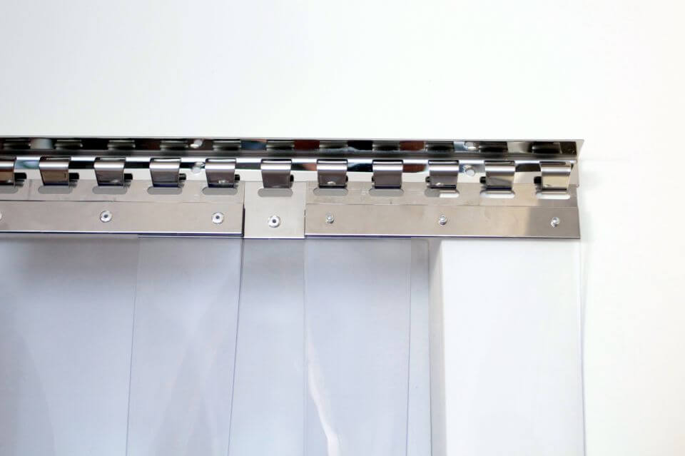 Zawieszanie okutych pasów PCV na zamocowanym do ściany wieszaku grzebieniowym