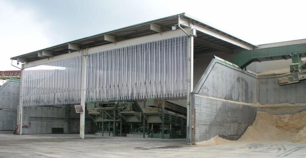 Kurtyny przemysłowe z pasów PCV zawieszone na wiacie w żwirowni