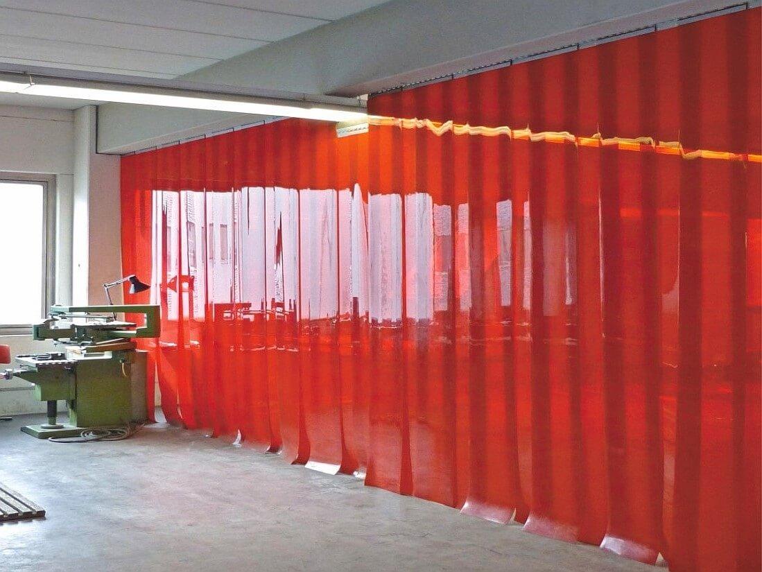 Kurtyna spawalnicza z pasów w kolorze czerwonym jako ścianka oddzielająca pomieszczenia.