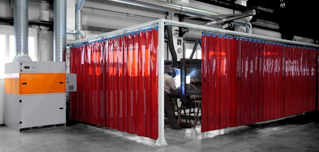 Kurtyny spawalnicze z lameli w kolorze czerwonym zawieszone na konstrukcji stalowej, osłaniają stanowisko spawalnicze.