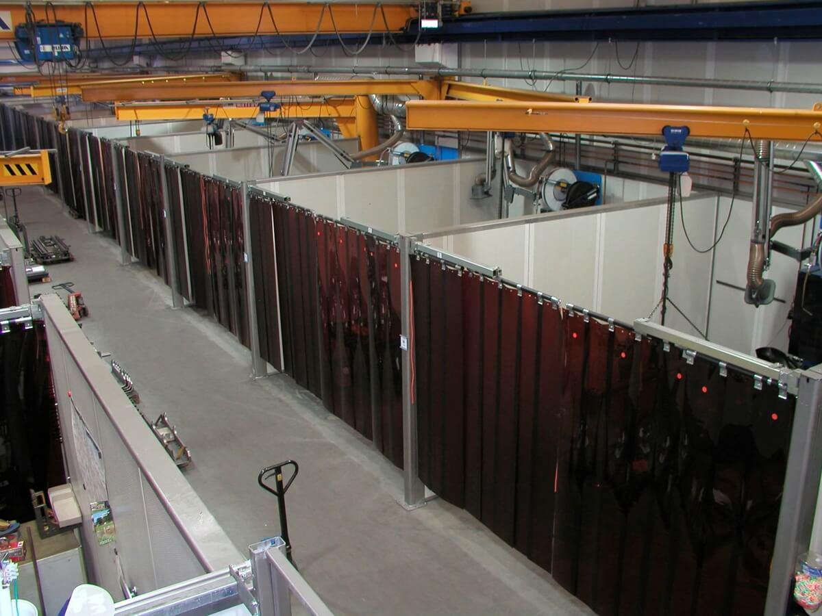 Kurtyny spawalnicze z lameli, zamontowane na wejściu do stanowisk spawalniczych.