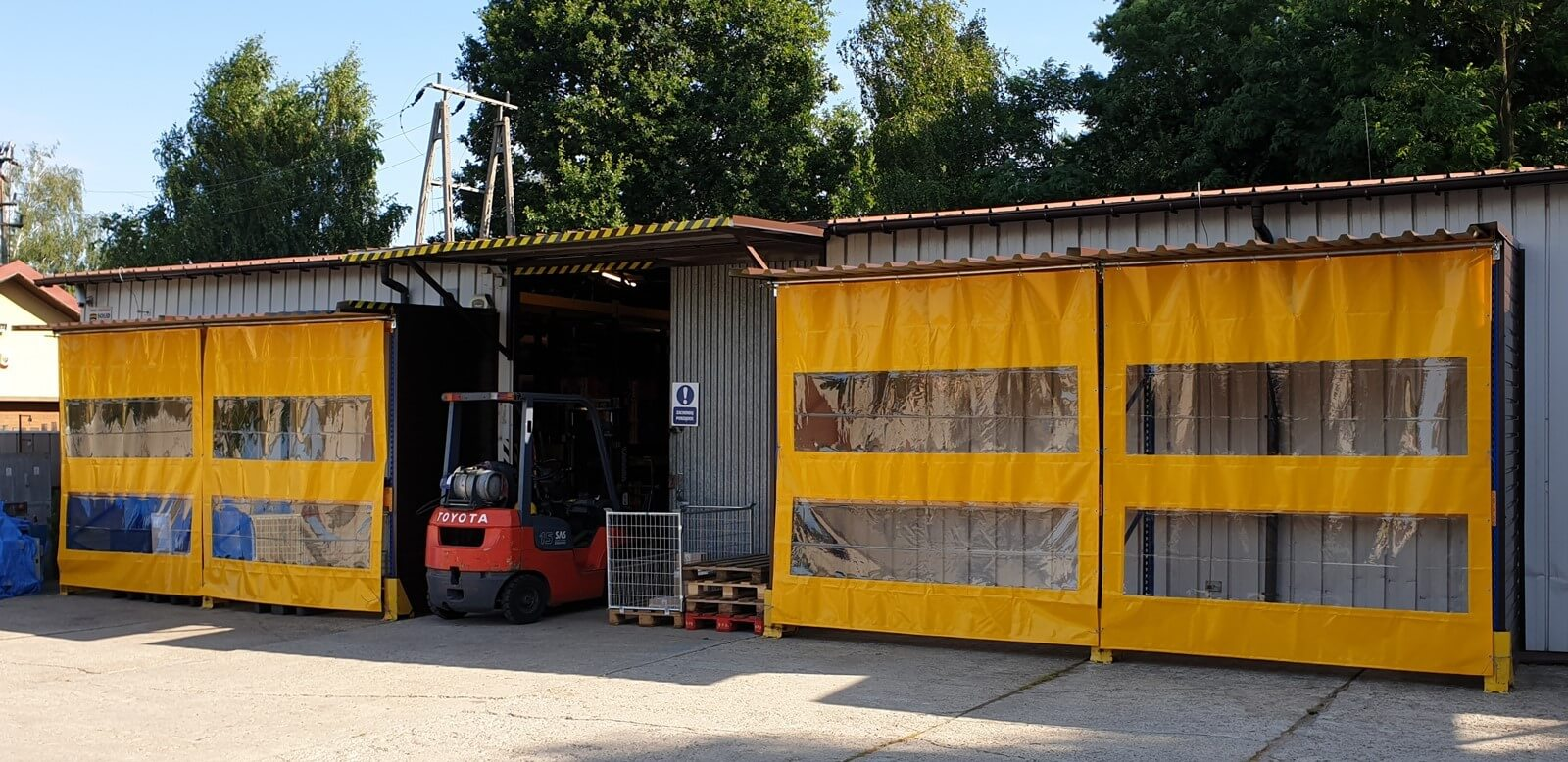 Kurtyny plandekowe w kolorze żółtym, z oknami, są zwieszone przy wiacie, jako zasłona dla regałów magazynowych
